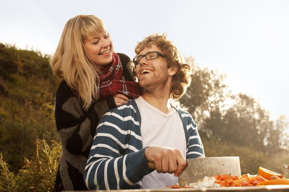 Young couple cutting vegetables outside