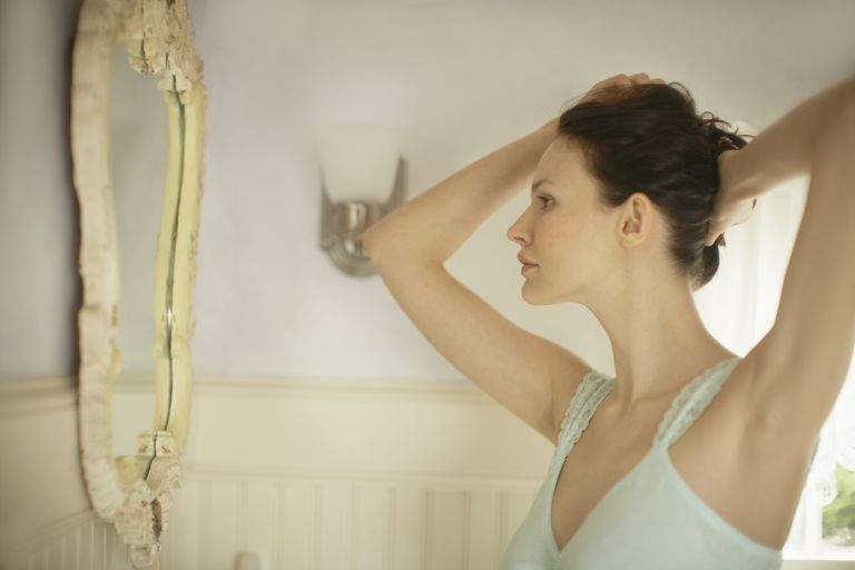 woman in camisole looking in mirror with hands overhead