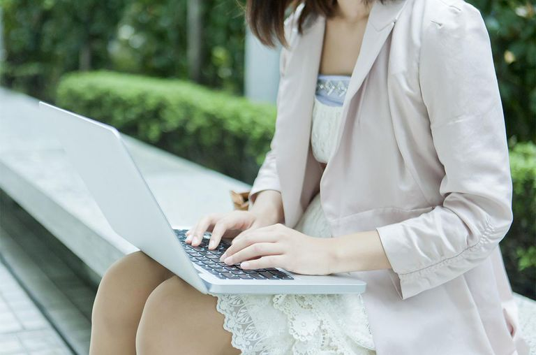 Young woman sitting on bench,using laptop