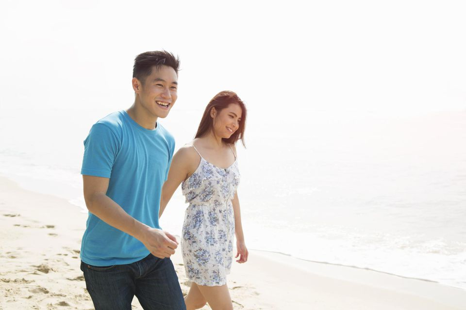 Young couple walking on beach smiling