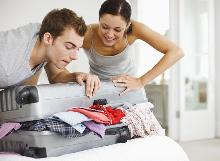 Couple trying to close full suitcase