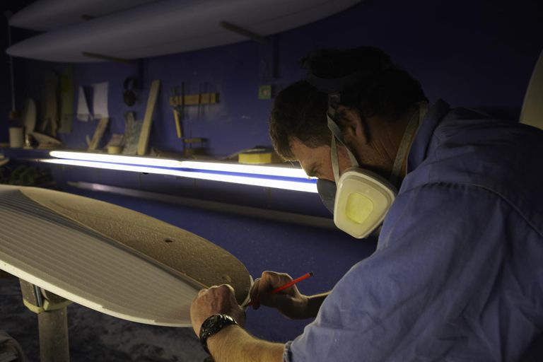 Surfboard shaper shaping surfboard