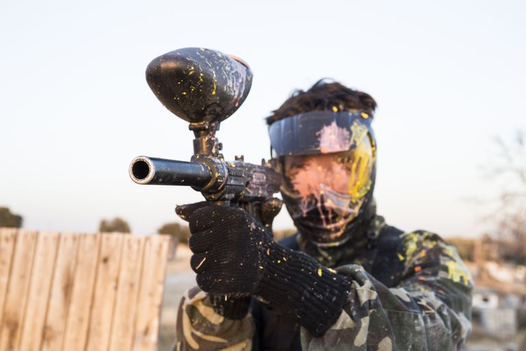 Paintball player with paintball mask and paintball gun stained with paint