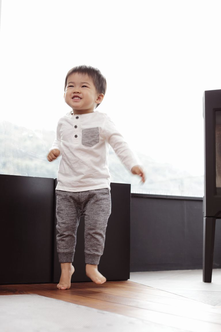 Baby boy jumping in living room,smiling