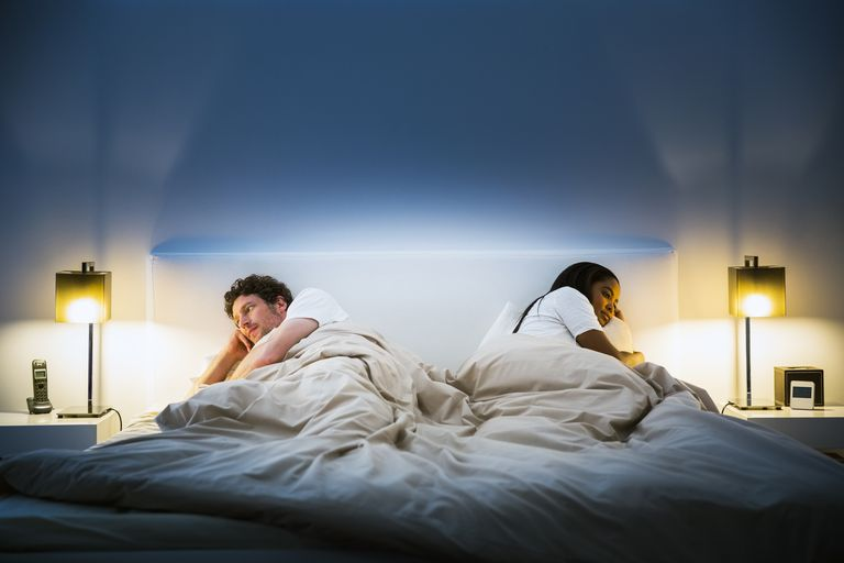 Couple turned away from each other in bed