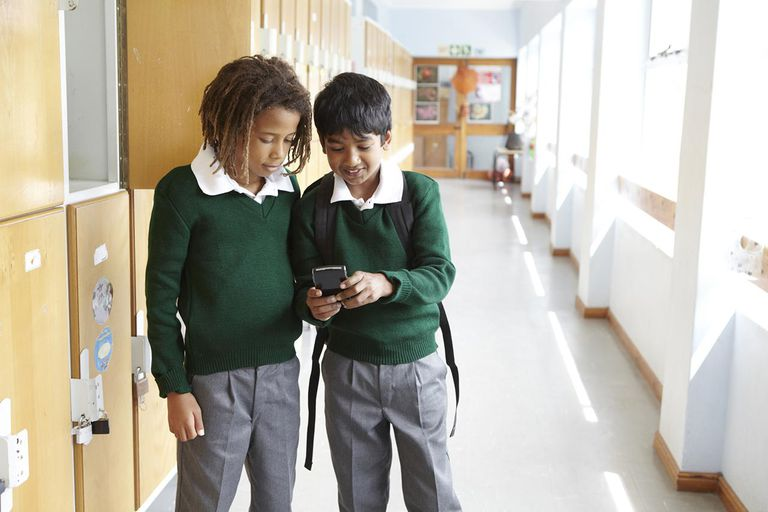 young boys using cell phone in school
