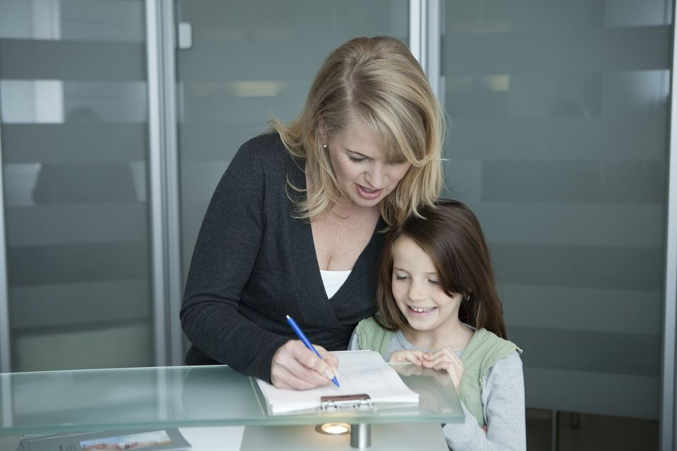 A picture of a mom and daughter filling out a form