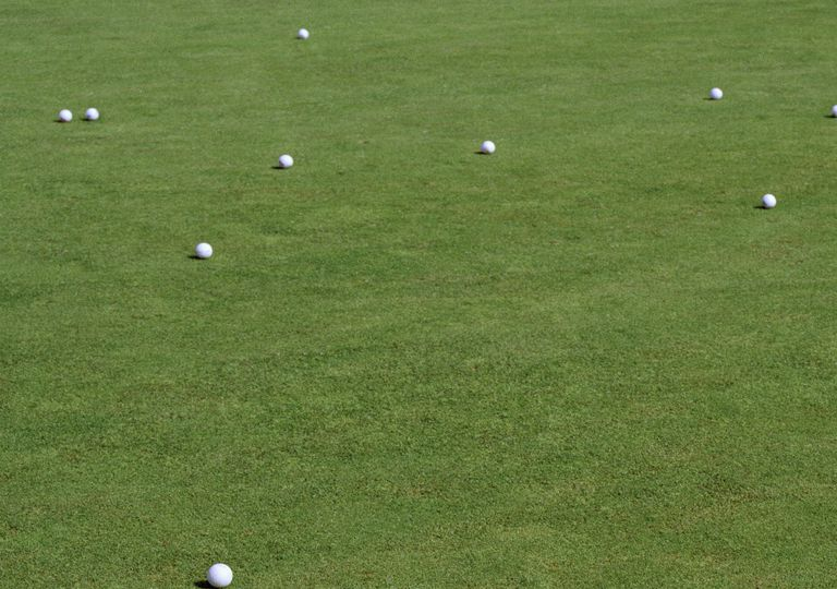many golf balls on a putting green