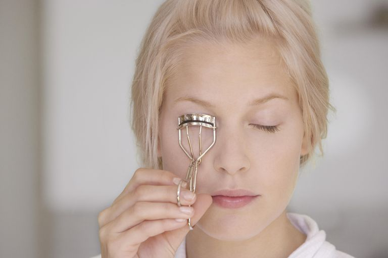 how to use eyelash curler. young woman using eyelash curler, eyes closed how to use curler