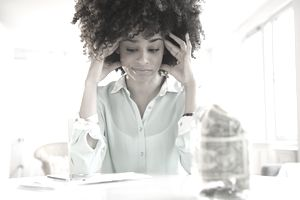Stressed mixed race woman paying bills