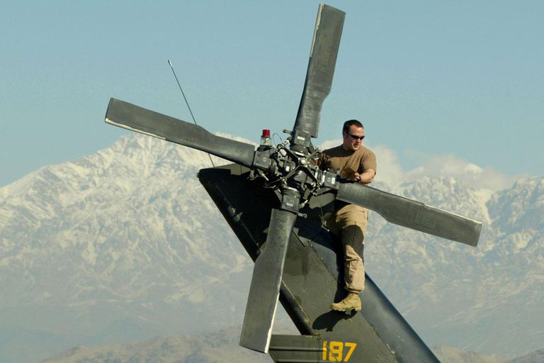 BAGRAM, AFGHANISTAN - JANUARY 31: A U.S. Army 82nd Airborne soldier, Sgt. Adam Hyland from West Palm Beach, Florida works on the tail rotor of a MH-60 Blackhawk while on the flight deck at Bagram military base January 31, 2003 in Bagram, Afghanistan.