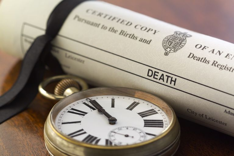 rolled up death certificate with black ribbon and pocket watch