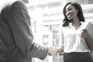 Business people shaking hands outside of office building