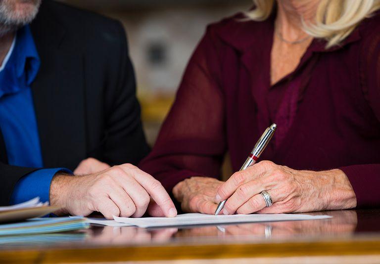 A senior citizen signing a document.
