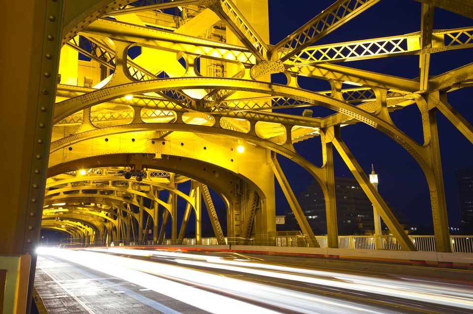 Cars pass under the famous Tower Bridge at night in downtown Sacramento, CA.