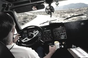 Man driving truck on desert road, view over shoulder, USA