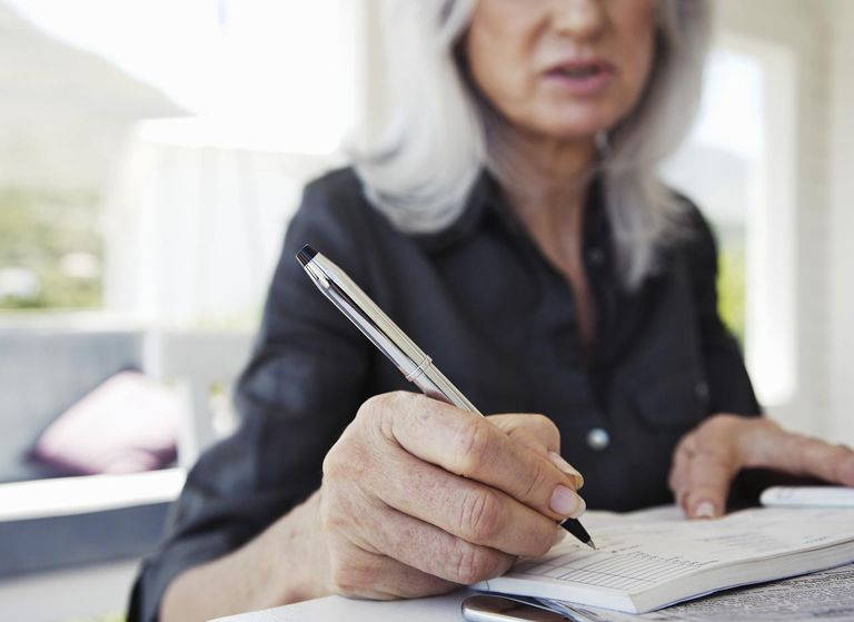 Mature woman writing in cheque book, mid section