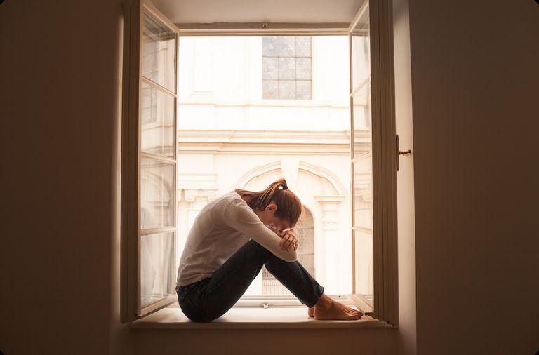 Sad woman alone in city apartment