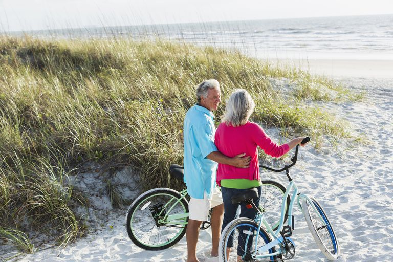 Couple with bikes in the sand looking at the ocean