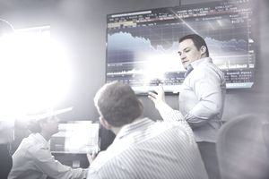 Colleagues in office pointing at wall mounted graphical screen having discussion