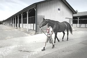 KY, Lexington, Man w/ horse in front of stables