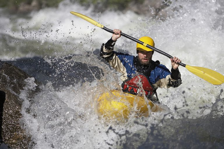 Man Paddling a White Water Kayak on a Idaho River.