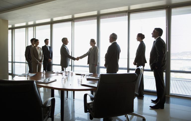 Business people shaking hands in conference room