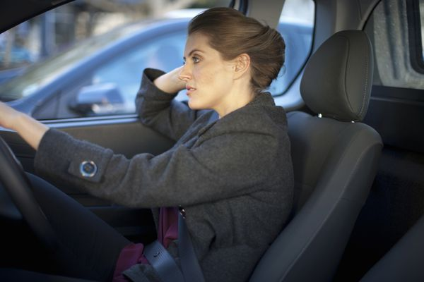 Young businesswoman driving in traffic congestion