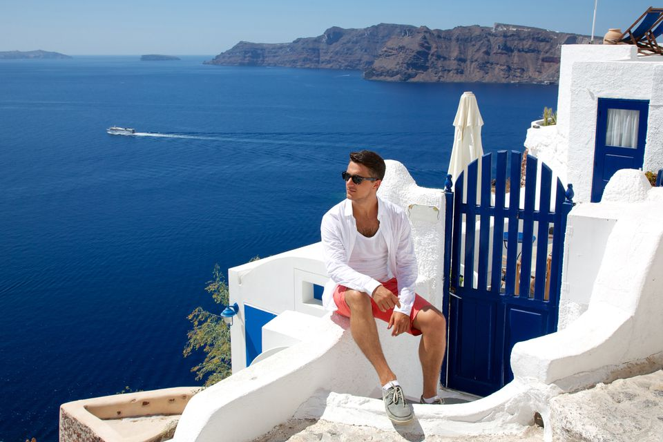 Young guy sitting near white house in Santorini