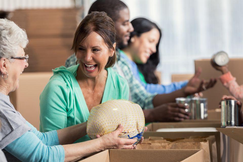 Female volunteers enjoy working together at community food drive