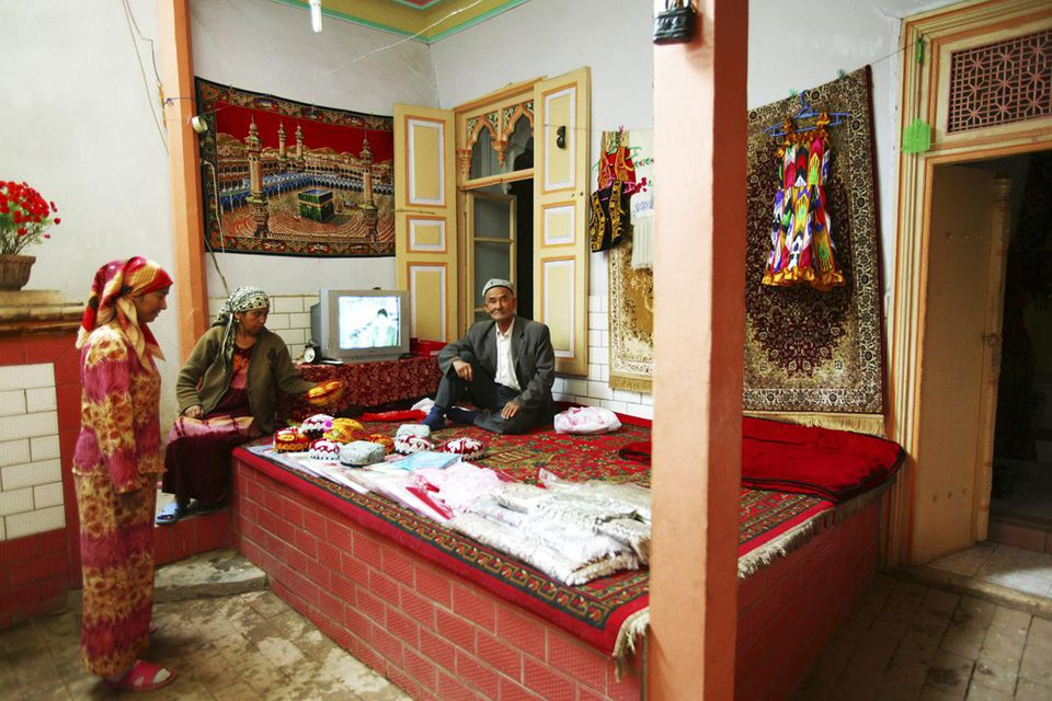 Uygur family in their traditional house, Kashgar Ancient Town, Xinjiang Uyghur Autonomous Region, China