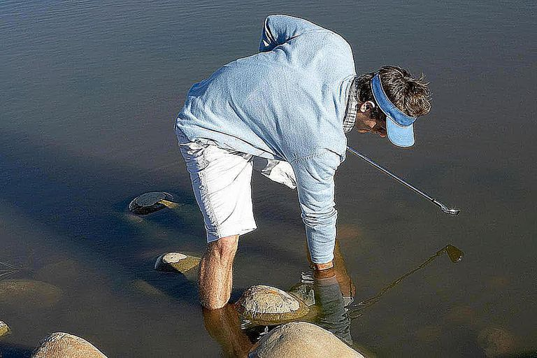 Man Searching for a Golf Ball in a Lake