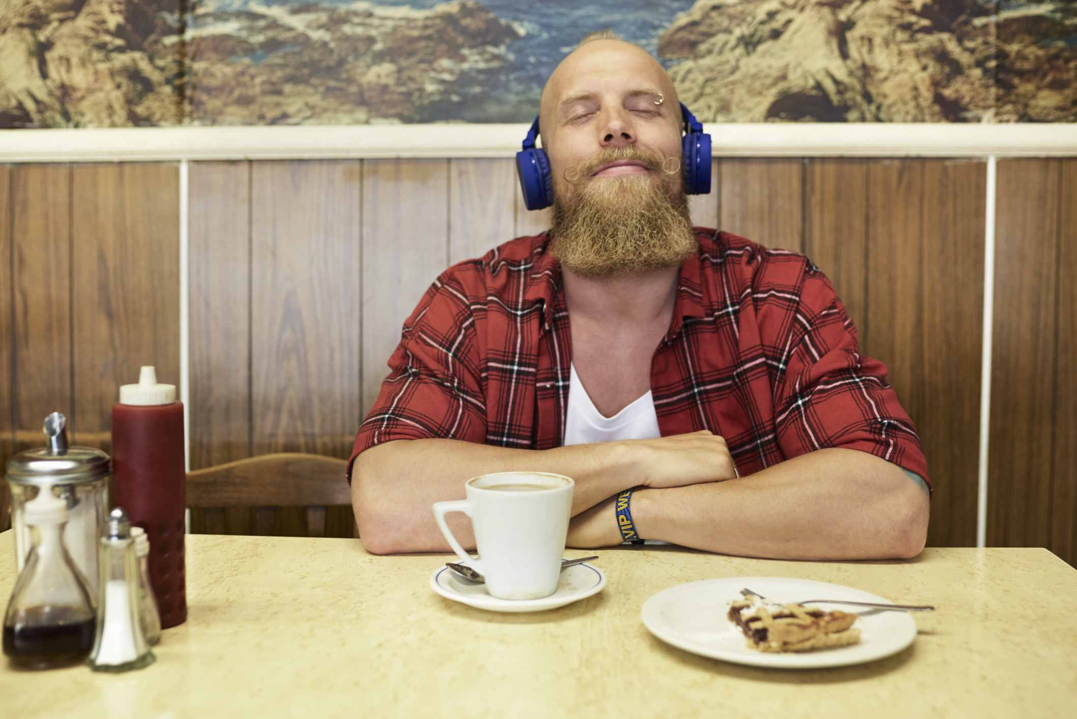 Man listening to wireless headphones in cafe