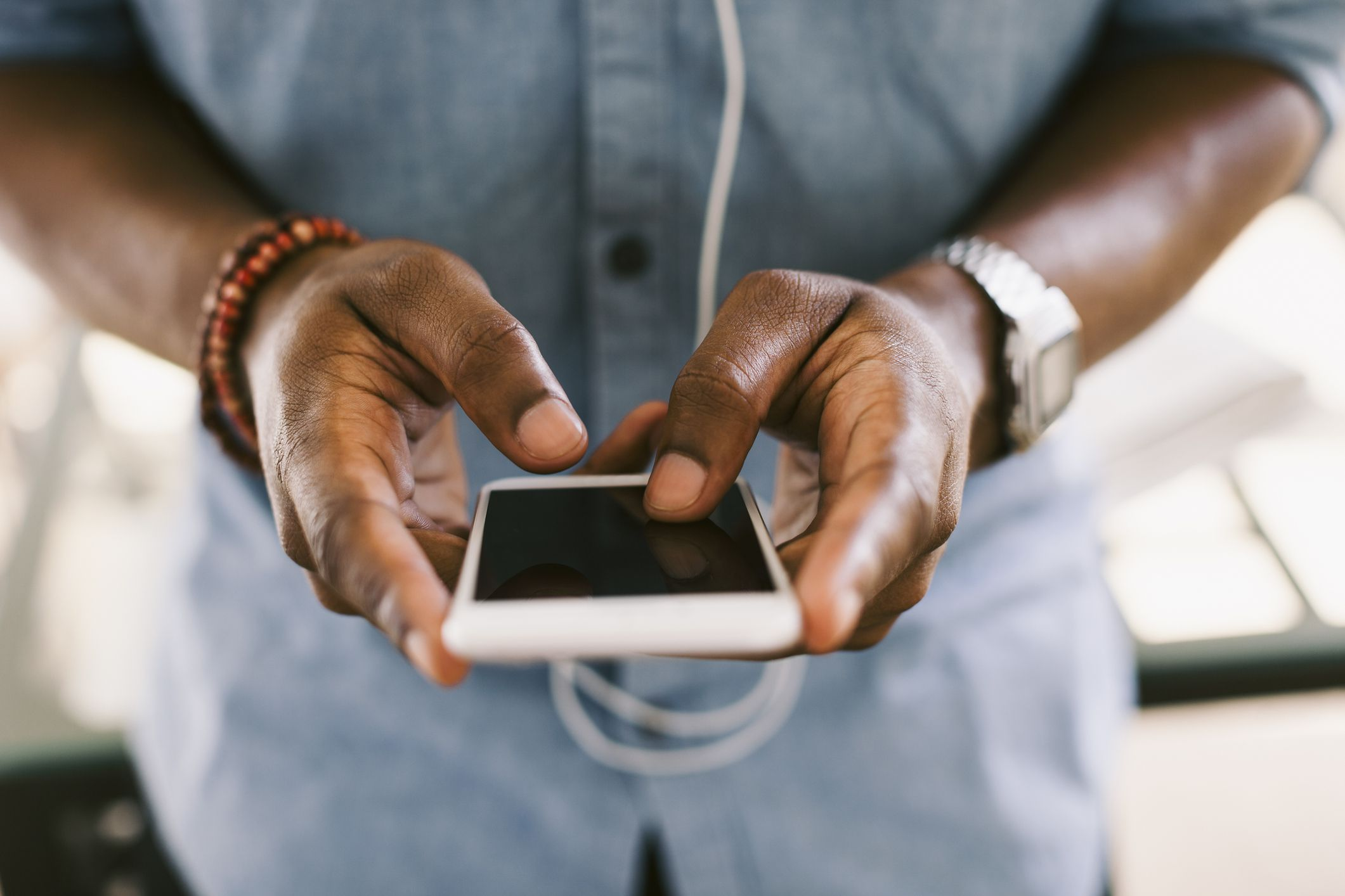 An mvno cell phone carrier resells network connectivity man texting on cell phone colourmoves