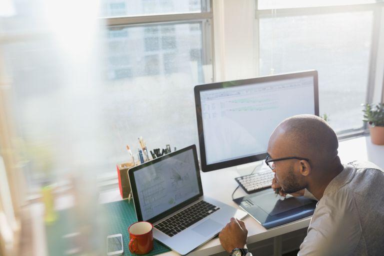 businessman on laptop and desktop computers