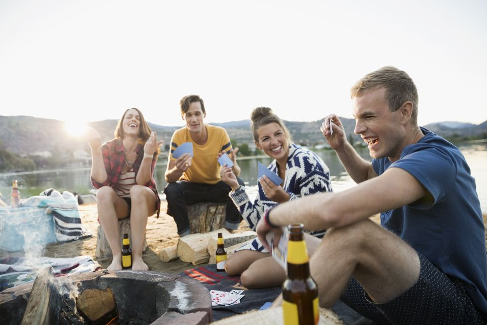 Young couples gesturing playing cards at summer beach campsite