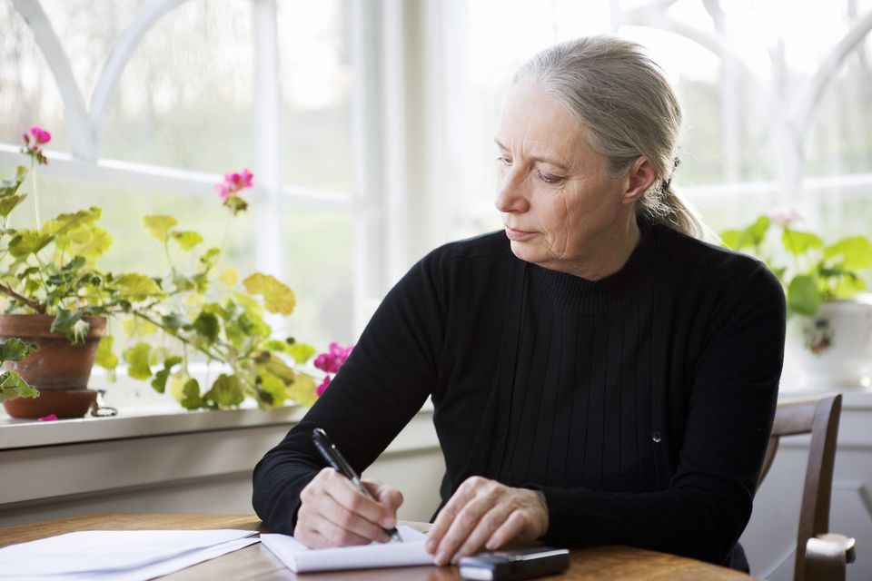 Senior woman writing at table by window