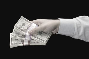 Hand outstretched holding money.