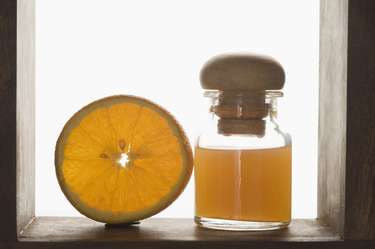Close-up of therapeutic oil with an orange half