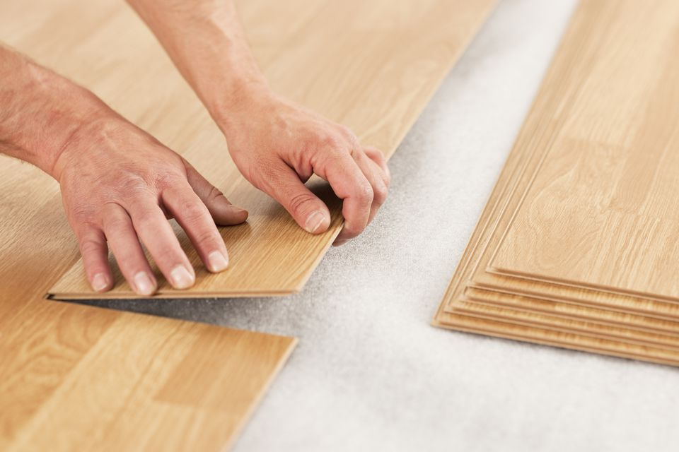 Picture of man's hands laying yellow laminate flooring