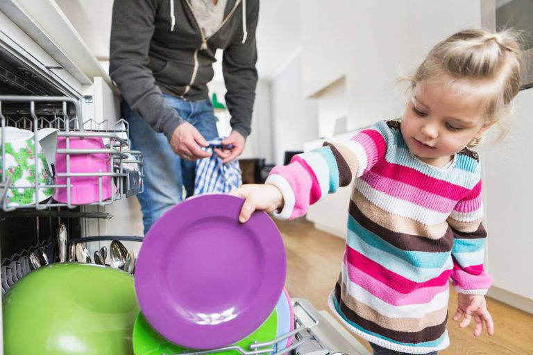 A picture of a responsible child loading the dishes