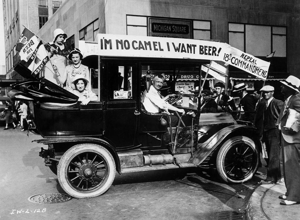 Prohibition protesters parade in a car emblazoned with signs and flags calling for the repeal of the 18th Amendment. One sign reads, 'I'M NO CAMEL I WANT BEER!' Photo by Archive Photos/Getty Images