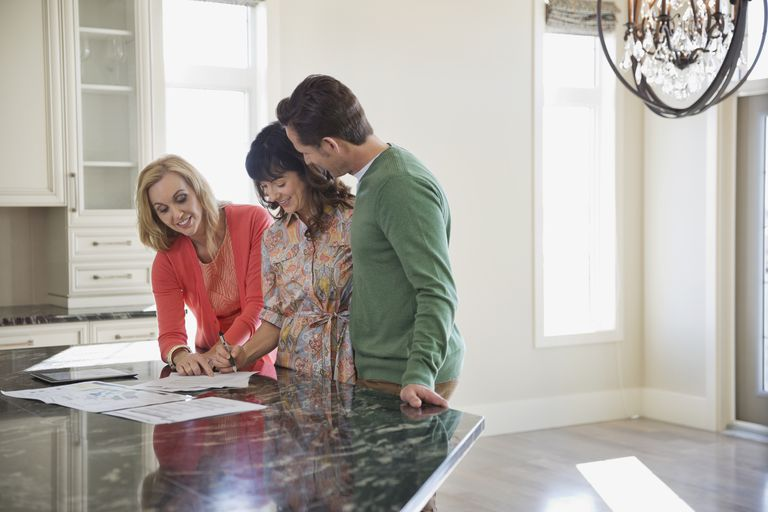 Female realtor discussing documents with couple at countertop