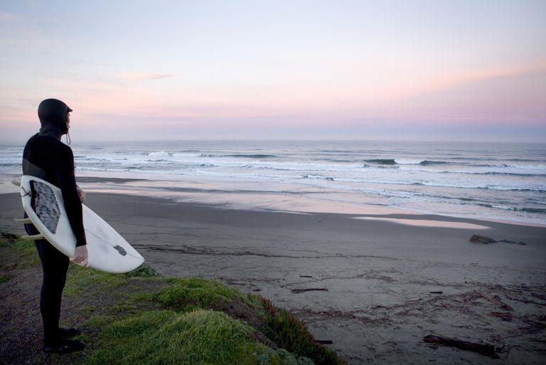 USA, California, surfer watching sunrise on beach