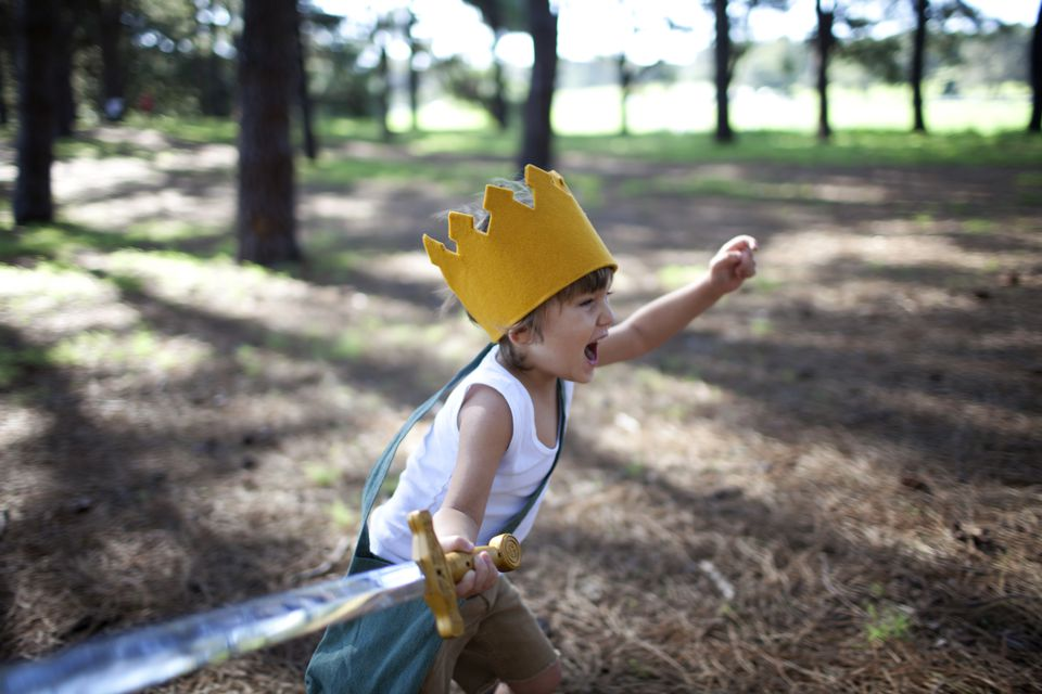 Little boy with crown running in forest with sword