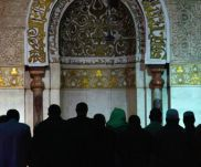 Men line up for prayers in front of the mihrab (prayer niche).