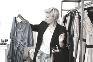 Woman selects and admires dress in store