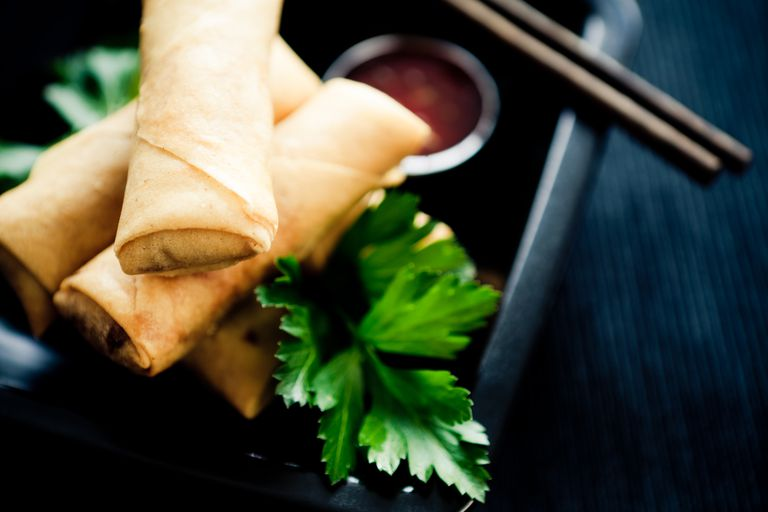 Photo of three spring rolls with sauce