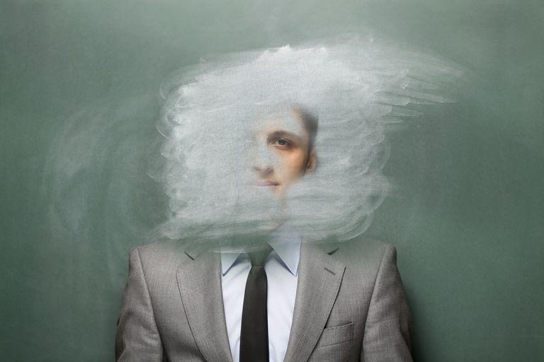 Hombre frente a la pizarra con la cabeza borrada
