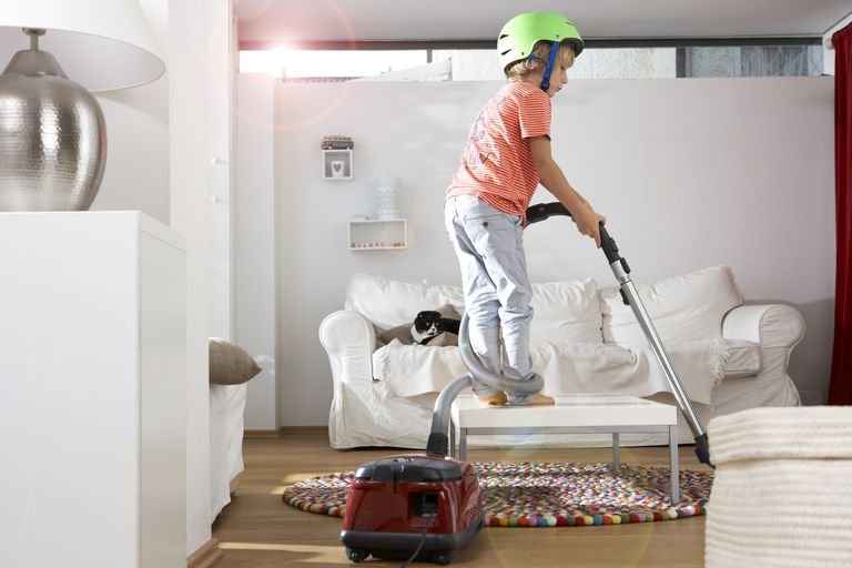 Boy in living room using vacuum cleaner